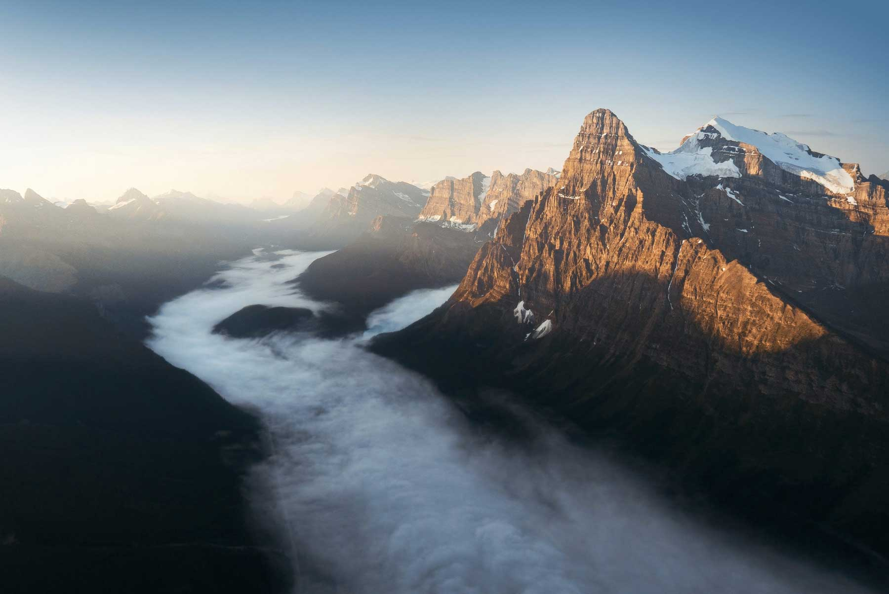 Aerial photography from a helicopter of mount chephren in Banff National Park during sunrise above the fog Photo by Andrew Studer