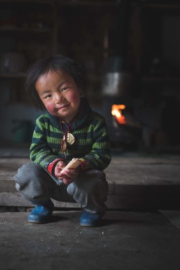 Portrait photography of a young boy sitting in Laya, Bhutan